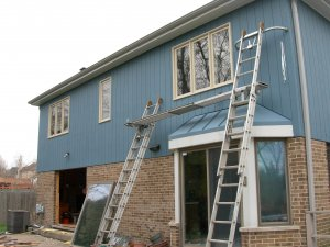 Back of a blue siding and brick home with ladders leaning against the house and new Marvin sliding glass doors and windows recently installed.